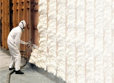 contractor spraying with foam a house wall